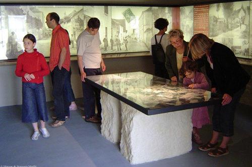 dans une salle de la Maison du Souvenir à Maillé, un groupe de visiteurs se penche sur une carte en relief