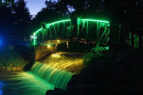 Un pont éclairé par des lumières colorées lors d'une manifestion son et lumière