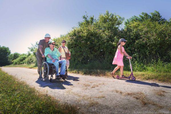 un groupe de personnes, dont une en fauteuil roulant, se baladent sur un sentier au bord de l'étang du Louroux