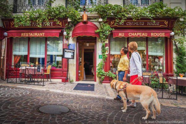 Un couple avec un chien guide d'aveugle regardent le menu affiché devant un restaurant