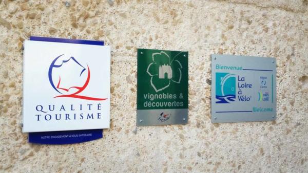 Trois pannonceaux de labels touristiques (Qualité tourisme, vignobles et découvertes et Loire à Vélo) sont accrochés sur un mur
