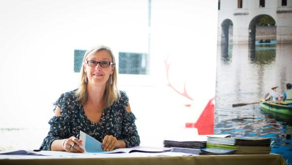 Une femme attablée à un bureau où sont empilées des brochures touristiques