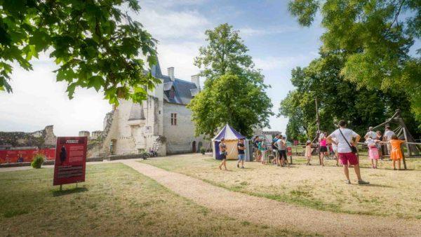 Des visiteurs se baladent dans la cour de la forteresse de Chinon occupée par une tente médiévale
