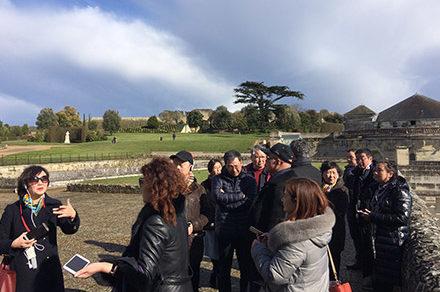 Un guide mène un groupe de visiteurs dan sla cour d'un château