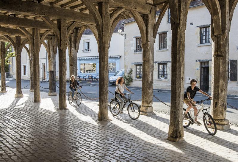 Un groupe de trois cyclistes circulent sous les halles médiévales de Montrésor